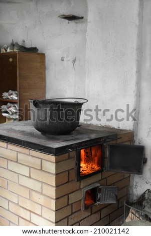 Old dirty boiler stands on burning rustic wood-burning stove - stock photo