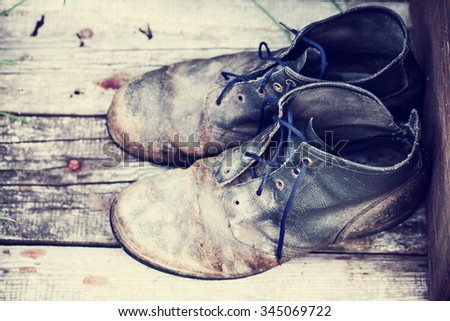 old dirty boots.old boots worn with scratches and untied shoelaces on grunge background - stock photo
