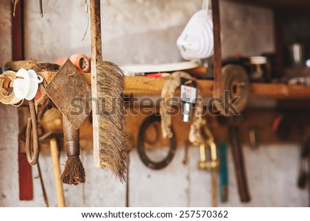 Old dirty cleaning brush hanging in the workshop on the shelf. - stock photo