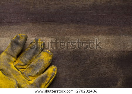 old dirty leather work glove on wood background - stock photo