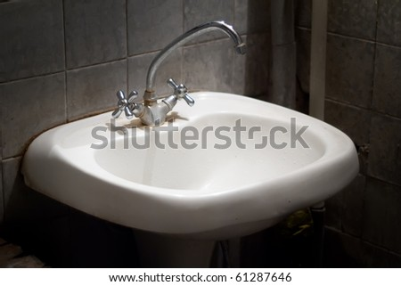 old dirty smelly sink in a dirty toilet - stock photo