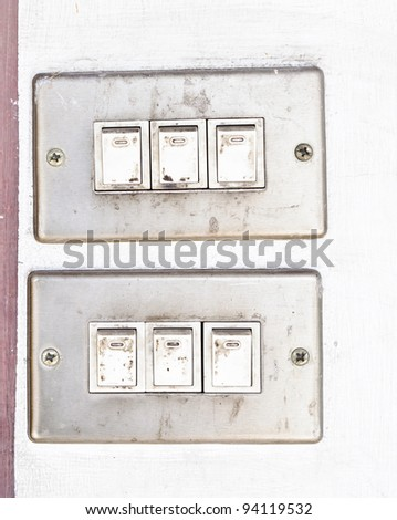 Old dirty switch on the white wall.