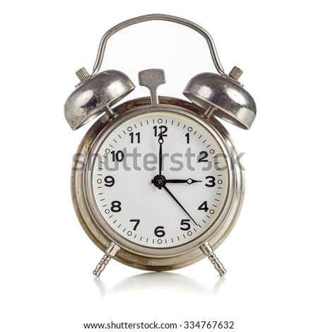 Old dirty vintage metal alarm clock showing three o'clock on white background - stock photo