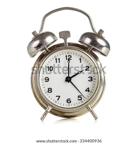 Old dirty vintage metal alarm clock showing two o'clock on white background