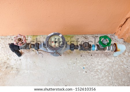 Old dirty water meter and rusting valve - stock photo