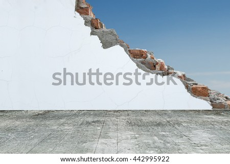 Old dirty wooden floor with cracked bricks wall and blue sky
