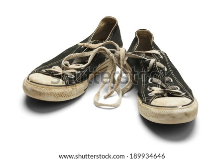 Old Dirty Worn Pair of Canvas Shoes With Knot in Shoe Laces Isolated on White Background. - stock photo