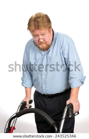 Old disabled man uses a walker to help keep from falling down as he moves around. - stock photo