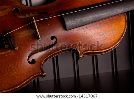 Old distressed violin with one string, leaning against black beadboard wall - stock photo