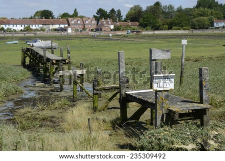 Old disused and broken wooden jetty at Bosham in Chichester Harbour. West Sussex. England. Low tide with exposed seaweed - stock photo