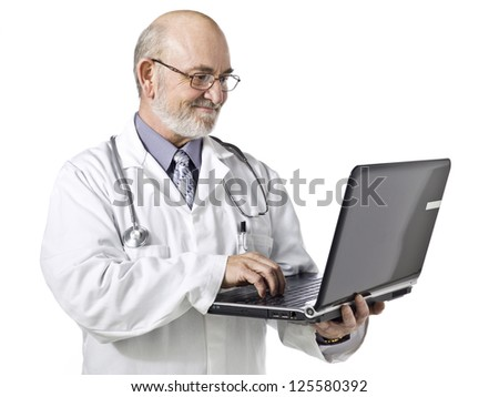 Old doctor using a laptop isolated in a white background - stock photo