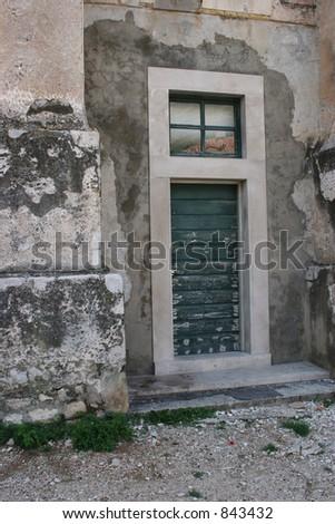 Old door in Dubrovnik, Croatia.  Red soda cap on ground. - stock photo