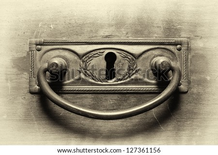 Old drawer handle in sepia tone - stock photo