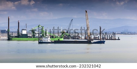 Old dredge boats in italy early in the morning - stock photo