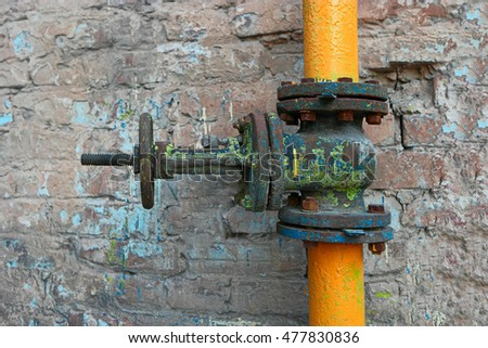 Old dusty and rusty valve and pipes of yellow color on weathered brick wall.