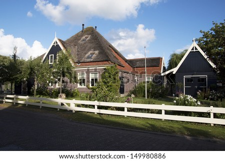 Old Dutch farm with a roof made of reed  - stock photo