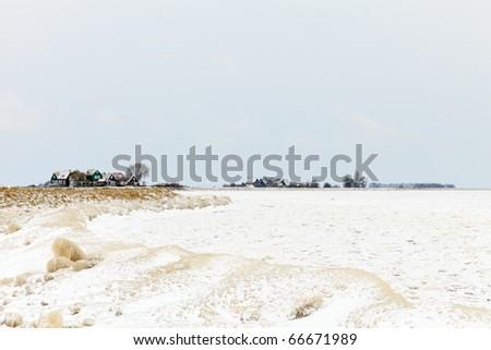 Old Dutch village near frozen sea in winter, Marken, the Netherlands - stock photo