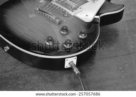 old electric guitar on old wooden floor - stock photo