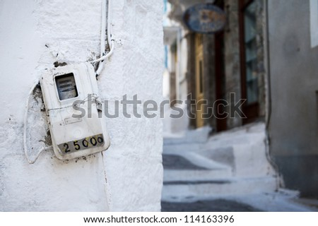 Old electric meter on a wall in a small street in a traditional Greek village - stock photo