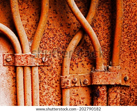 Old electrical cables on a rusty iron wall - stock photo