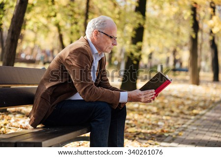 old elegant man with gray hair reading a book outside in park - stock photo