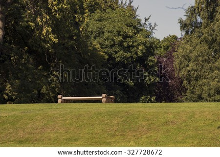 Old empty bench in a Danish park with a forest background. - stock photo