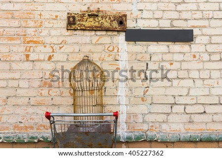 Old empty bird cage in old rusty shopping cart sticking outside of painted brick wall with weather iron plates above it - stock photo