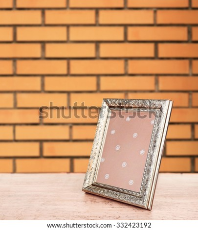 Old empty frame standing on table on brick wall background - stock photo