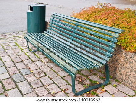 Old empty wooden city bench and trashcan