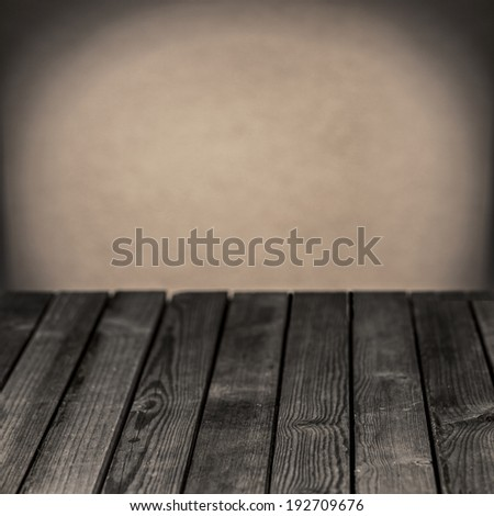 Old empty wooden rustic table in a grunge gloomy grey room with a central highlight on the blank wall behind for your placement of your food - stock photo