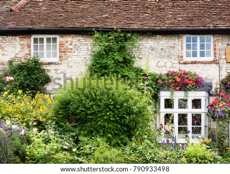 Old English Cottage House With Wild Flower Garden View Of Facade Windows And Plants