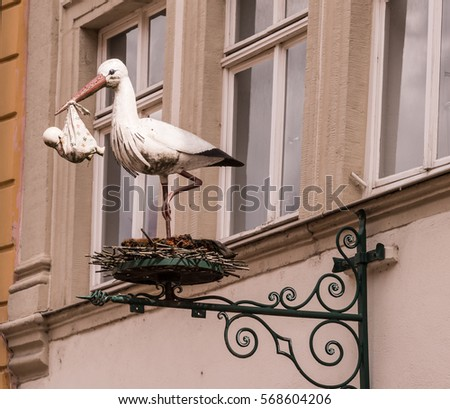 Old European Store sign of a Stork carrying a Baby