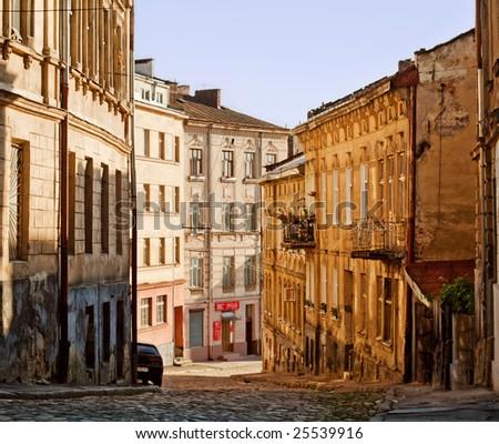 Old european town narrow street in the morning - stock photo
