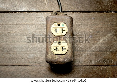 Old extension cord on wooden table - stock photo
