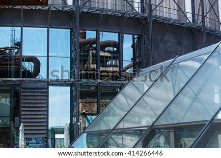 Old factories reflection in the windows of a modern building - stock photo