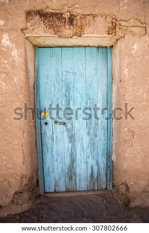 Old faded wooden colonial door and adobe architecture in a small village in Potosi State. Bolivia - stock photo
