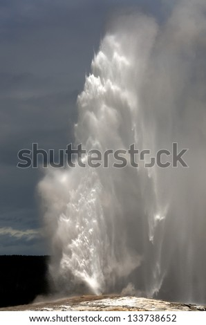 Old Faithful Geyser erupting in Yellowstone National Park in Wyoming in the United States of America - stock photo
