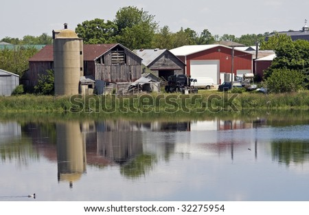 Old farm reflected in the pond - stock photo