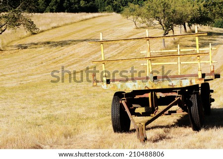 old farm trailer in harvested field