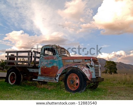 Old farm truck in sunset - stock photo