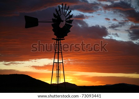 Old Farm Windmill for Pumping Water with Spinning Blades at Sunset in South Africa - stock photo