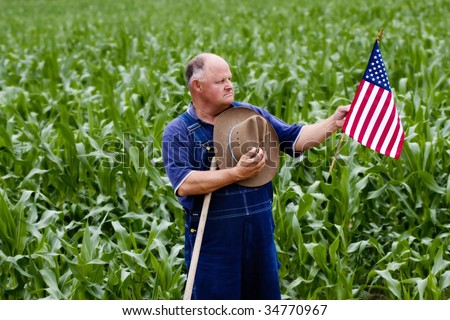 Old farmer displays his American pride by holding the U.S. flag - stock photo