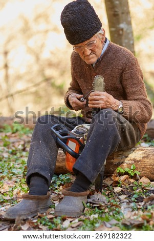 Old farmer doing maintenance work to his chainsaw
