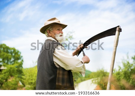 Old farmer with beard sharpening his scythe before using to mow the grass traditionally - stock photo