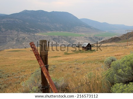 Old farmhouse in a field near Lillooet, British Columbia, Canada - stock photo