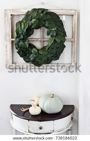 Old farmhouse window decorated with a homemade Magnolia leaf wreath hung on an interior wall over rustic half moon table with heirloom pumpkins.