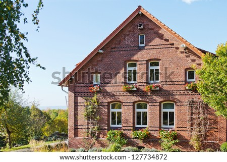 Old farmhouse with plantings in Germany in front of a blue sky - stock photo