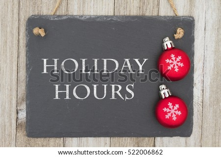 Old fashion Christmas store message, A retro chalkboard with Christmas ornaments hanging on weathered wood background with text Holiday Hours