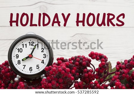 Old fashion Christmas store message, Frost covered red holly berries with an alarm clock on weathered wood background with text Holiday Hours