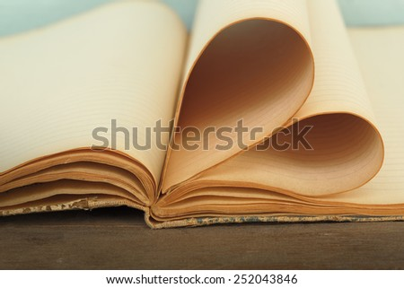 Old fashion notebook pages folded as heart sign - stock photo